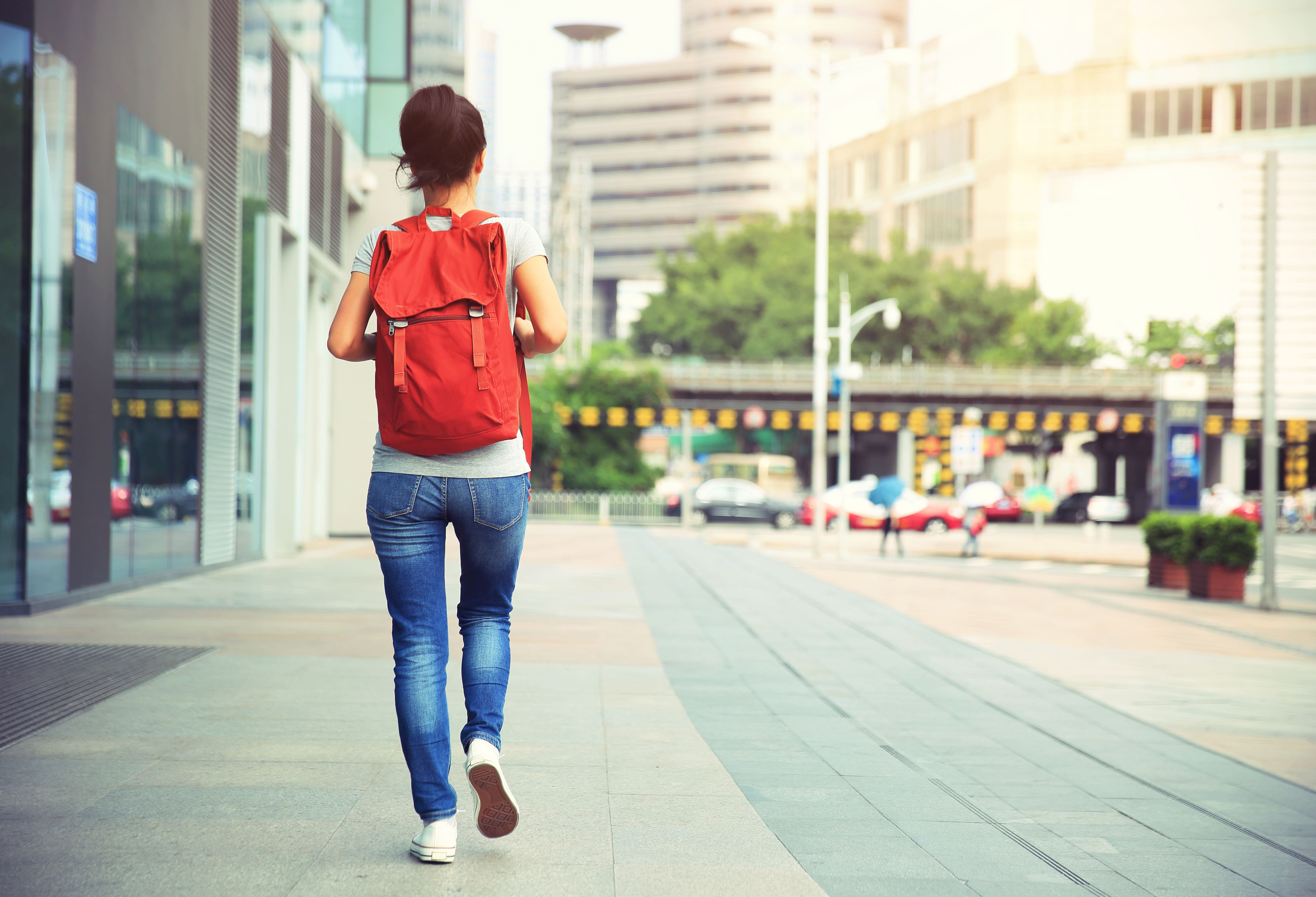 woman-with-rucksack-walking-on-street-PEJXBSD-min.jpg